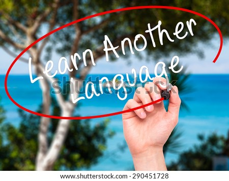 Man Hand writing Learn Another Language with black marker on visual screen. Isolated on nature. Learn, technology, internet concept. Stock Image