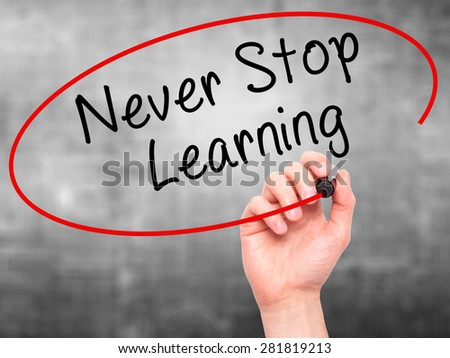Man hand writing Never Stop Learning on visual screen. Business,help, internet, technology concept. Isolated on grey. Stock Photo