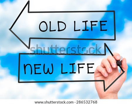 Man hand writing Old Life or New Life on visual screen. Business, help, internet, technology concept. Isolated on sky. Stock Photo