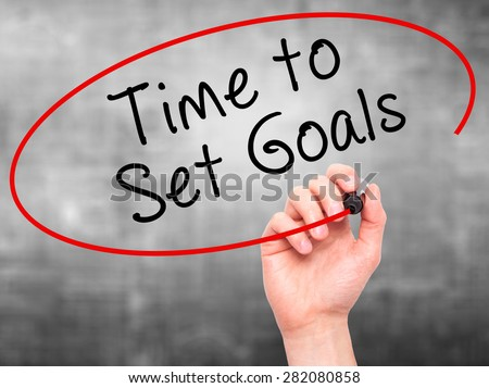 Man hand writing Time to Set Goals on visual screen. Business,help, internet, technology concept. Isolated on grey. Stock Photo