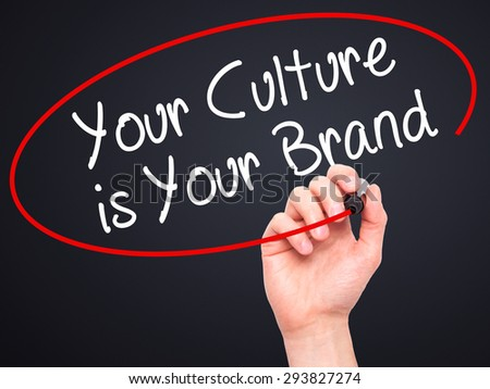 Man Hand writing Your Culture is Your Brand with black marker on visual screen. Isolated on black. Business, technology, internet concept. Stock Photo