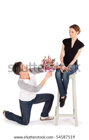 Man handing over bouquet of flowers to a beautiful young woman on Valentine Day isolated on white background