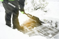 Man handle black shovel or snow sled and  removing snow from stairs sidewalk during eavy snow storm. Safety in winter concept.