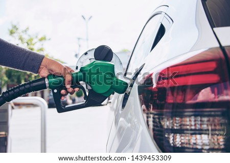 Photo of  Man Handle pumping gasoline fuel nozzle to refuel. Vehicle fueling facility at petrol station. White car at gas station being filled with fuel. Transportation and ownership concept.