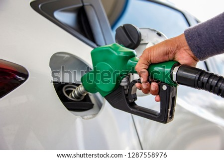 Man Handle pumping gasoline fuel nozzle to refuel.Vehicle fueling facility at petrol station. White car at gas station being filled with fuel. Transportation and ownership concept. Right side Europe