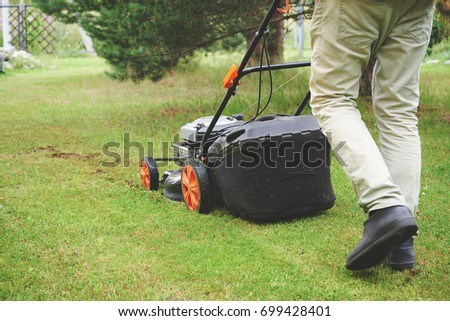 Man handling lawn with lawnmower. #699428401