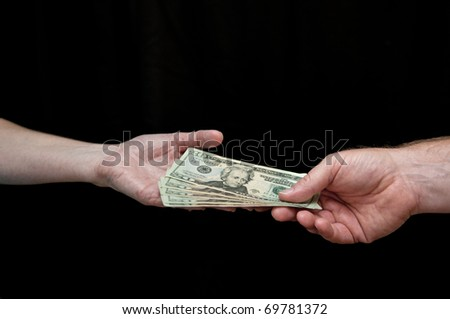 Man hands a woman money. Black background. Cutout.