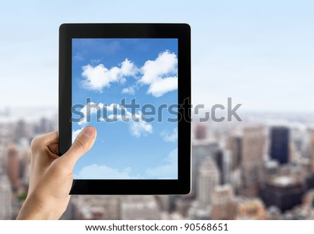 Man hands are holding contemporary digital tablet with cloudscape on screen. Concept image on cloud-computing theme. Blurred cityscape with skyscrapers on background.