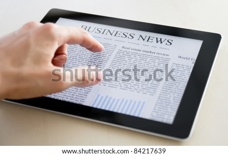 Man hands are pointing on touch screen device with business news.