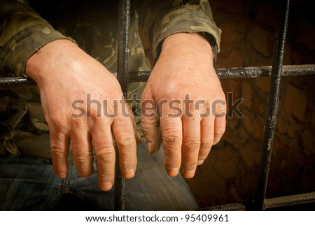 Man hands behind the bars against brick wall