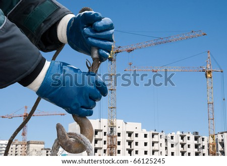 man hands closeup with crane hook at building background