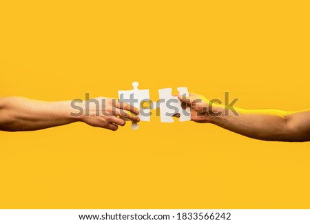 Man hands connecting couple puzzle piece. Business solutions, target, success, goals and strategy concepts. Hand connecting jigsaw puzzle. Business solutions, success and strategy concept. Photo stock ©