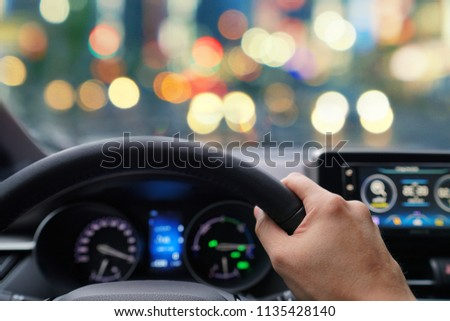 Man hands driver on steering wheel of a modern car with Car dashboard and beautiful sky background.Traffic jam on rush hour in the city.Transport,Vacation,Holiday,Travel and Automobile Concept. #1135428140