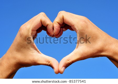 man hands forming a heart over the blue sky