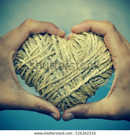 man hands forming a heart showing a heart-shaped coil of rope