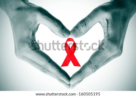 man hands forming a heart with his hands and a red ribbon for the fight against AIDS on a white background