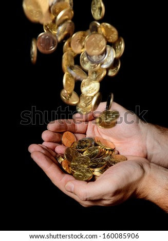 Man Hands full of money receiving a Rain of Coins isolated on black background