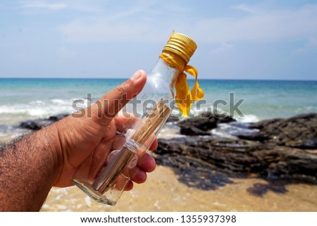 man hands holding a bottle with message inside - message in a bottle.         #1355937398