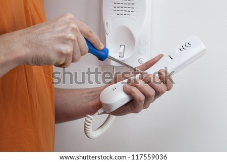 Man hands holding and repairing handset of entry phone