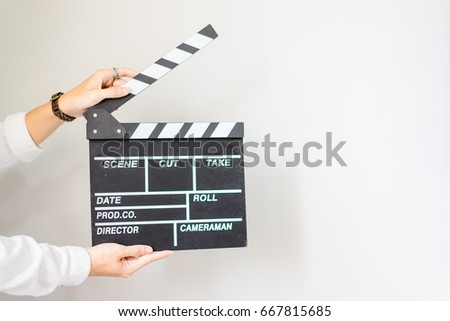 Photo of  man hands holding clapper board for making video cinema in studio.Movie production clapper board or slate film concept.
