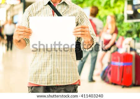 Man hands holding empty signboard at international airport meeting point - Young casual guy with blank sign for advertising text is receiving travelers at arrival  gate -  Main focus on male hands