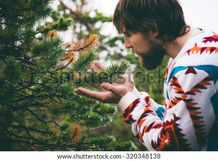 Man hands holding fir tree branch Travel Lifestyle survival concept outdoor forest nature on background
