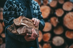 Man Hands Holding Firewood. Unrecognizable male caring wood logs to the house, to start a fireplace. Rustic countryside background, still life. slow living.