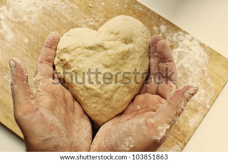 Man hands holding homemade heart shaped pastry on a wooden board
