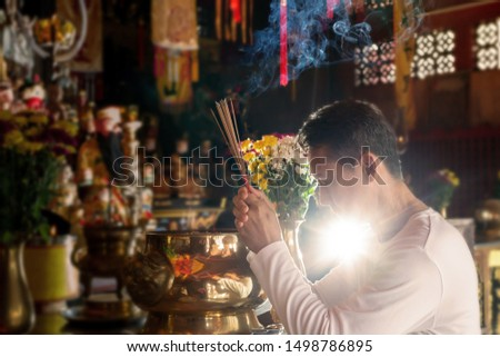 Man hands holding joss sticks praying and blessing in front of altar table at chinese shrine with blurred gods statue in background.Faith and religious.