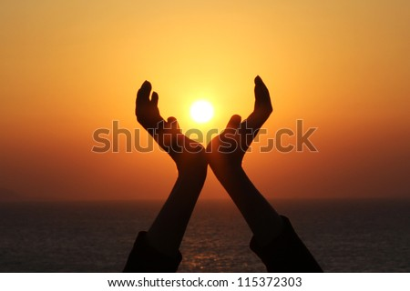 man hands holding the sun at sunrise