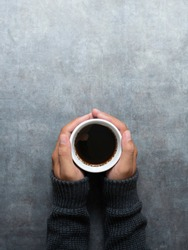 Man hands in grey sweater holding cup of coffee on the stone table