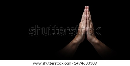 Man hands in praying position low key image. High Contrast isolated  on Black Background. Banner