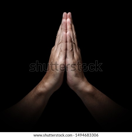 Man hands in praying position low key image. High Contrast isolated  on Black Background. Ratio 1:1