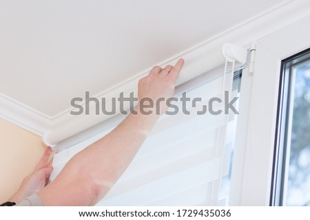 Man hands installing window roller duo system day and night.
