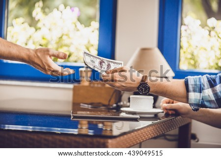 man hands money to another man. man sitting in the cafe gives money to another man