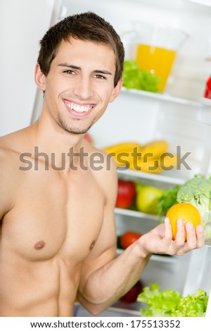 Man hands orange standing near the opened fridge. Concept of healthy and dieting food