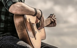 Man hands playing acoustic guitar, close up. Acoustic guitars playing. Music concept. Guitars acoustic. Male musician playing guitar, music instrument.