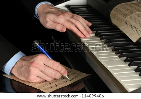 man hands playing piano and writes on parer for notes ストックフォト ©