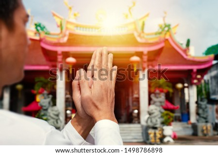 Man hands pressing together praying and blessing in front of  chinese shrine at sunrise .Faith and religious.