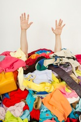 Man hands reaching out from a big pile of clothes and accessories. Man buried under an untidy cluttered woman wardrobe. Man reaching for help from to much woman shopping.