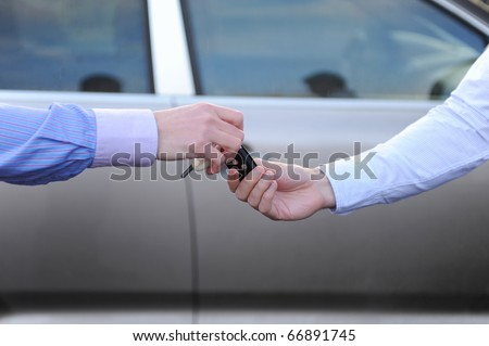 man hands the keys to the car