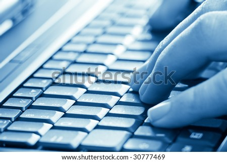 man hands typing on laptop keyboard blue toned