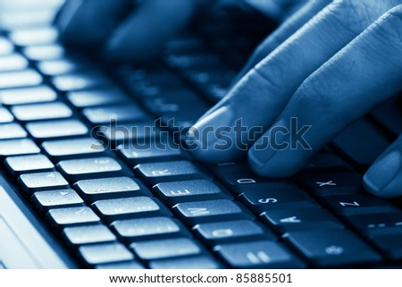 man hands typing on laptop keyboard blue toned with shallow depth of field