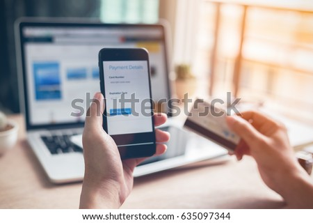 Man hands using smartphone and laptop computer for online shopping at home, Hand holding mobile phone with Payment Detail page display and credit card, online shopping concepts #635097344