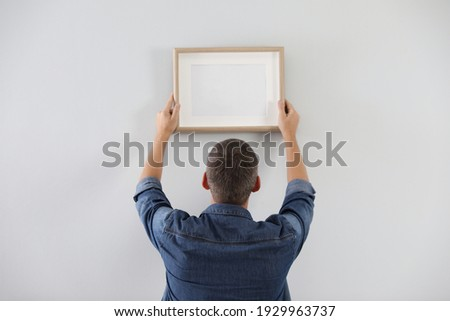 Man hanging picture on white wall indoors. Interior decoration Foto stock ©