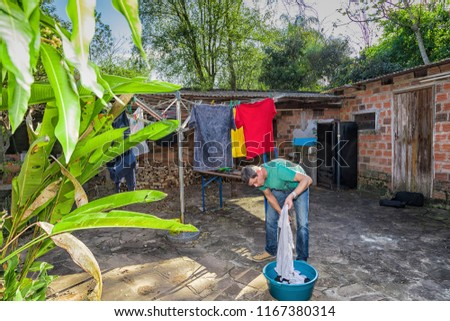Man hangs laundry in the garden on a clothesline. #1167380314