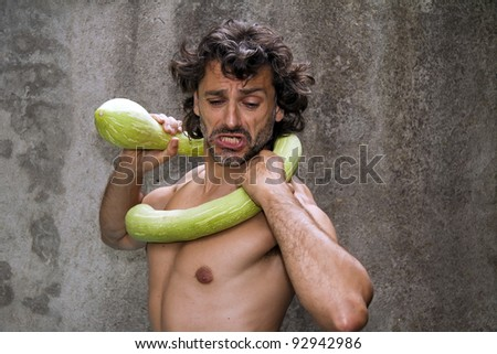 man have a funny fight with a big zucchini squash