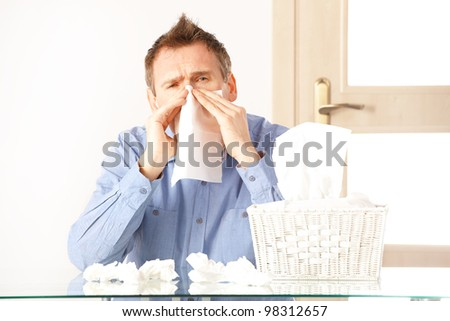Man having a cold holding tissue with box full of tissues