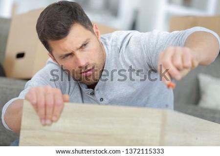 man having a hard time assembling the furniture