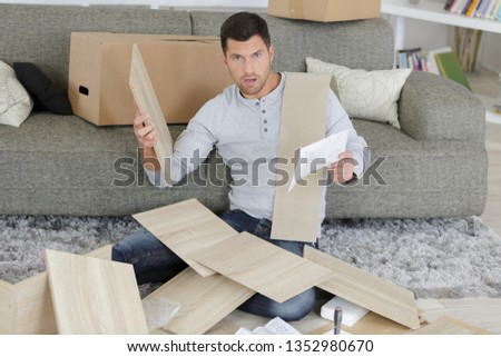 man having a problem with furniture assembling